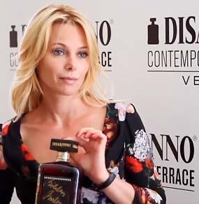 Un'attrice regge una bottiglia di DiSaronno da lei autografata