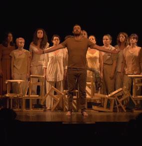 Un uomo su un palcoscenico con le braccia aperte con dietro degli sgabelli e un gruppo di persone vestite di bianco