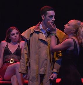 Una donna tocca il viso di un uomo in impermeabile mentre una seconda donna guarda seduta dietro di loro in abiti succinti