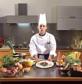 Un cuoco mostra un piatto sul tavolo di una cucina dove sono presenti molti ingredienti colorati tra cui notiamo delle parti umane come mani e orecchie
