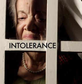 Una donna anziana dietro una finestra con aria disgustata e la scritta Intolerance sopra un infisso bianco