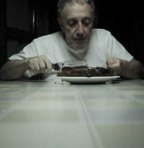 Un uomo anziano seduto a tavola mangia un dolce con una paletta da cucina