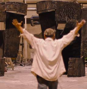 Salvatore Cuschera con le braccia alzate va verso una sua scultura