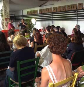 Alcuni spettatori seduti su sedie colorate seguono un uomo che parla e notiamo la scritta Ciao Teatricoltori
