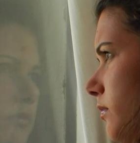 Primissimo piano di una ragazza di profilo che guarda fuori dalla finestra dove vediamo la sua immagine riflessa