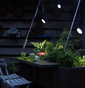 Una struttura con piante e un piano da tavolo fotografata di sera con luci di atmosfera
