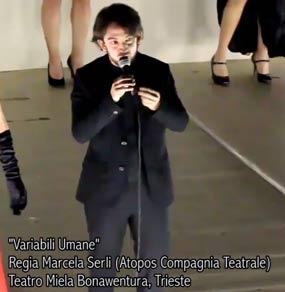Un uomo in abito nero parla al microfono su un palco e vediamo scritte in sovrimpressione nella parte bassa della foto