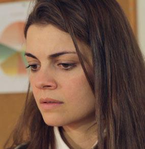 Primo piano di una ragazza coi capelli lunghi che guarda in basso e dietro di lei un grafico a torta appeso ad una bacheca di sughero
