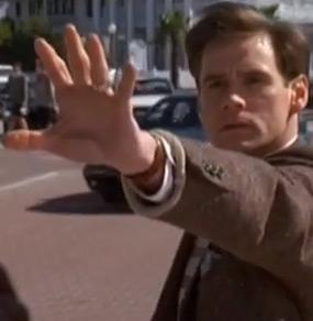Jim Carrey nel film Truman Show è in strada ed ha il braccio sinistro allungato verso di noi con la mano aperta in segno di voler fermare qualcosa