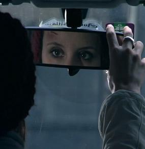 Una donna si specchia nel retrovisore di una macchina e ha una ferita sulla fronte