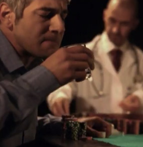 Un uomo ad un tavolo da gioco beve controvoglia un bicchiere di sciroppo osservato da un croupier con camice medico e stetoscopio