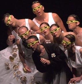 Un gruppo di attori con abiti bianchi tranne quello in primo piano con giacca nera e occhiali da piscina gialli
