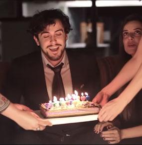 Un ragazzo sorride illuminato solo dalle candeline di una torta che gli viene avvicinata da quattro mani