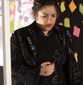 Una donna con una giacca nera con delle scritte a mano con espressione concentrata e la mano vicino al petto e sullo sfondo di tanti fogli colorati post it e un poster