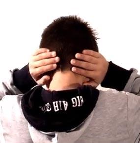 Un bambino di spalle si copre le orecchie davanti ad uno sfondo bianco