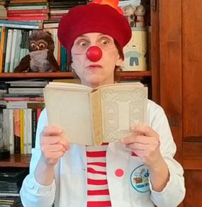 Un Clown Dottore legge un libro con un'espressione di stupore