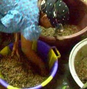 Una donna di colore con abito tipico e foulard in testa si piega a lavorare del sapone a scaglie dentro tinozze colorate