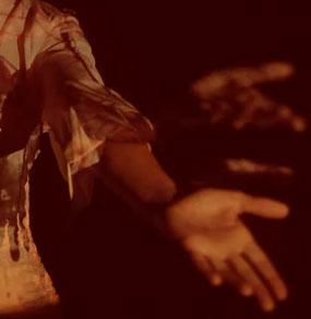 Un mezzobusto di donna di cui non vediamo la testa e in primo piano la sua mano triplicata in dissolvenza seguendone il movimento