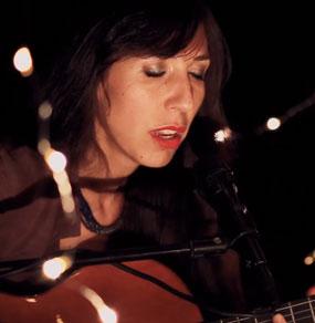 Anna Vignozzi canta un brano live con chitarra e occhi chiusi, in esterni notturni con lucine di atmosfera